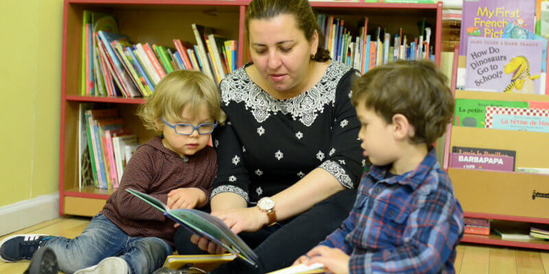 a woman reads a book to two young boys as they sit in front of a bookshelf in a French preschool in New York