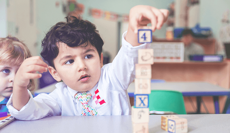 a boy puts a wooden block on top of a tower of other wooden blocks on a table in a French preschool in New York