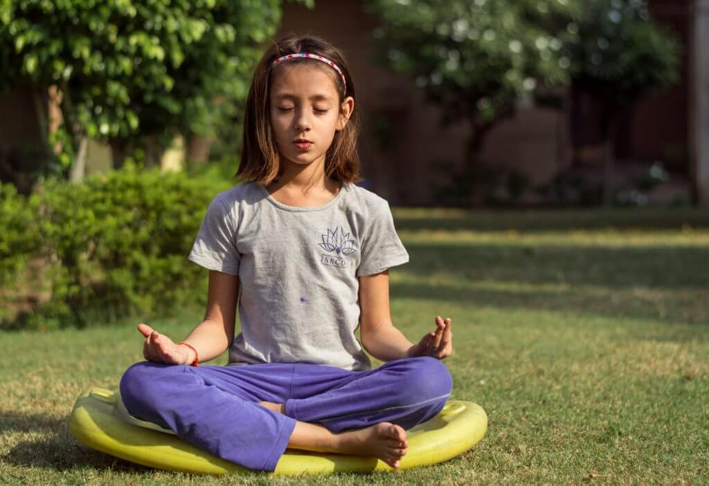 a girl sits cross-legged on a yellow mat on the grass with her eyes closed as she meditates