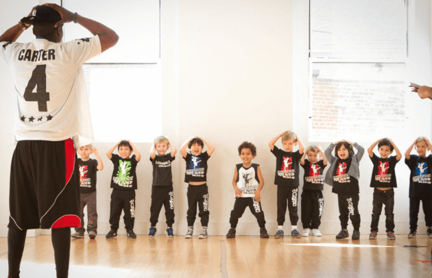 boys mimic a teacher as he puts his hands behind his head in a dance class for boys