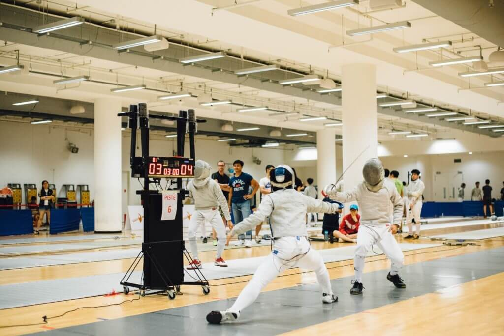 two opponents in white clothing fence each other near a digital game timekeeper while people watch on