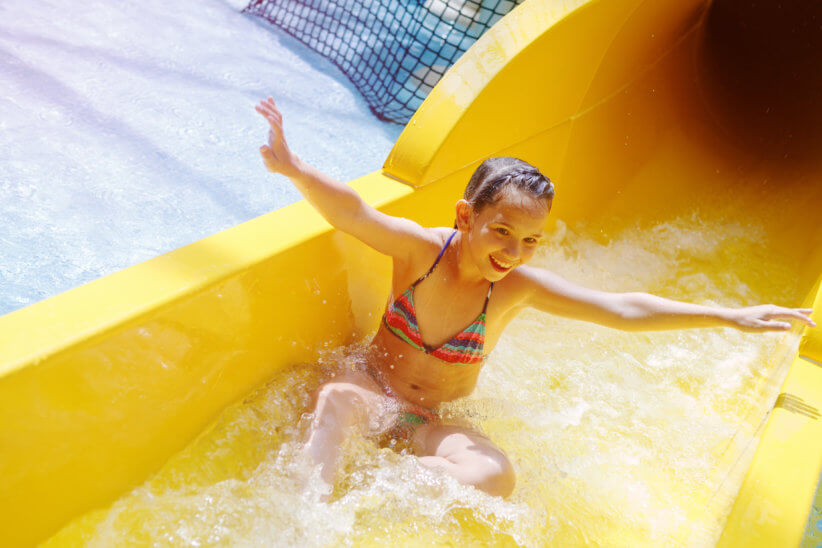 girl going down a slide at an indoor waterpark